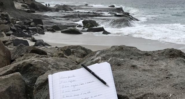 Image of notebook filled with personal mantras sitting on the rocks at the beach